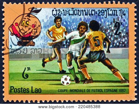LAOS - CIRCA 1982: a stamp printed in Laos shows soccer players in action, 1982 World Cup Soccer Championships, Spain, circa 1982