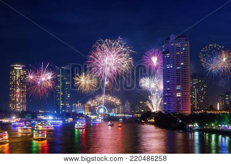 Firework downtown Happy New Year in Bangkok City Thailand. View form Taksin Bridge with chaopraya river.