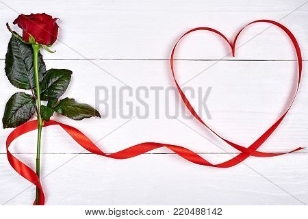 Valentines Day background with one red rose and ribbon shaped as heart, copy space. Greeting card mockup for Valentines Day, Womans Day (March 8, Mothers Day. Love, wedding concept. Top view, flat lay