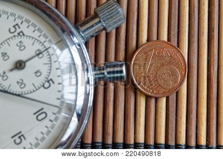 Stopwatch and coin with a denomination of one euro cent on wooden table background