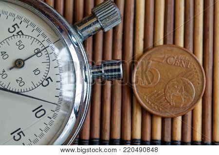 Stopwatch and coin with a denomination of five euro cents on wooden table background