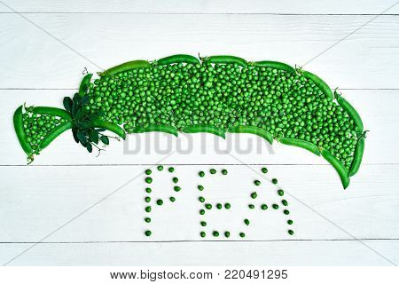 Top view of green pea pod made from fresh green peas and pods on white wooden background, copy space. Flat lay. Food natural background