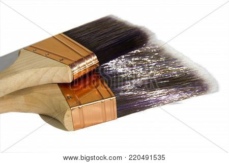 Two large synthetic high quality paint brushes on a white isolated background.