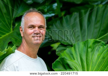 Attractive middle-aged man with a tall lush green plant of Hawaiian Philodendron giganteum behind him showing the relative height of the leaves of the plant