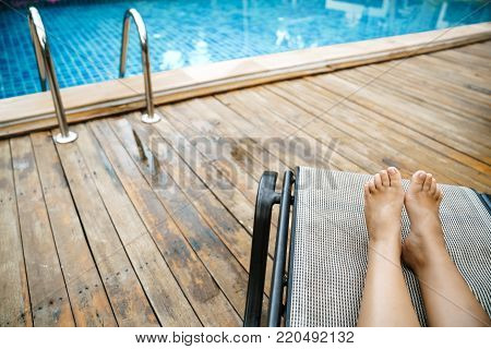 Beautiful Legs Girl relaxing near swimming pool in hotel, feet , happy beach holidays Luxury holiday near the pool.