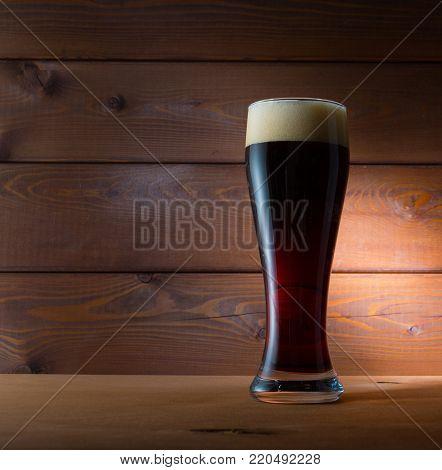 Glass of dark beer on wooden background