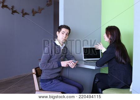 Beautiful young woman and men laugh and chat on abstract topics, sitting in office at computer. Gay students gossip about classmates and smile. European-looking man dressed in white shirt and blue striped cardigan with blue pants, European-looking woman