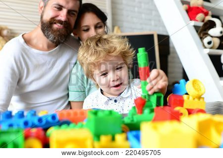Young Family Spends Time In Playroom. Family And Childhood