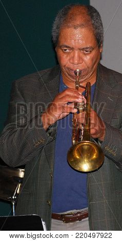 African american male jazz trumpet player performing in a nightclub.