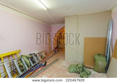 Unfinished interior of upgrade room with ladder  and constructional materials during on the remodeling, renovating, extension, restoration, reconstruction and construction. ( making wall from gypsum plasterboard) poster