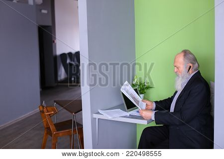 Grandpa working on pension communicates with potential business partners and negotiates bluetooth headset, reads and dictates information from documents, sits in modern office at table with laptop. Elderly man with long gray beard of European appearance