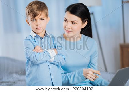 Moments of educational process. Upset little boy pouting, folding his arms across the chest and looking offended while his mother looking at him, having scolded for a mischief