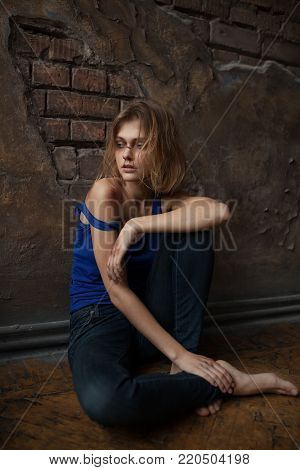 Beaten sad woman victim of domestic violence and abuse sits on floor with bruises and wounds on her face and body. Сoncept of domestic violence, sexual violence and cruelty.