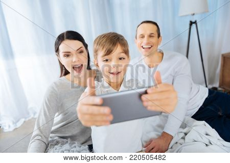 Best moments. Cheerful little boy taking a selfie with his upbeat parents posing for the camera and making funny faces while sitting on the bed