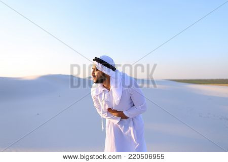 Worn-out Emirati man bends from pain and clings to stomach, suffers from severe pain and suffers with all strength, standing in midst of bottomless desert with snow-white sand on sunny summer day. Swarthy Muslim with short dark hair dressed in kandura
