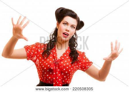 Portrait of terrified horrified young woman in red screaming shouting isolated. Girl with pinup makeup and hairstyle doing fun. Studio shot. Retro vintage style. Fear.