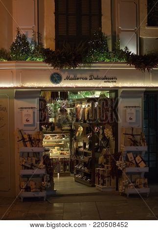 PALMA DE MALLORCA, BALEARIC ISLANDS, SPAIN - DECEMBER 5, 2017: Mallorca Delicatessen store front in Old Town shopping street with evening Christmas light decorations on December 5, 2017 in Palma de Mallorca, Balearic islands, Spain.