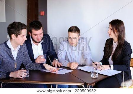 Three managers who are held discuss agenda and are waiting for start of business meeting with women's superiors. Young beautiful girl walks into office and greets her, sits on chair and starts meeting on working day, sitting at table in company's modern o