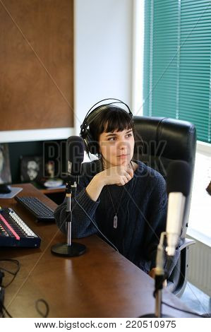 Young girl TV presenter with headphones on neck smiling and resting on air during commercials, sitting on chair in radio studio in office with large panoramic windows on desktop are microphones and mixing consoles, broadcast processor, special device and