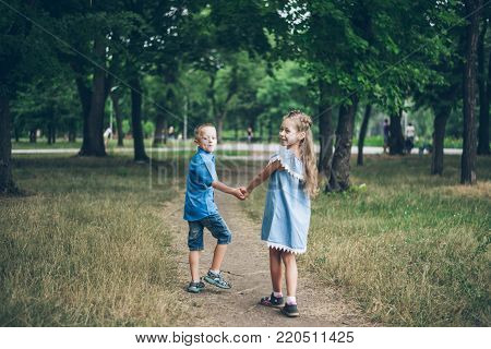 A little boy and girl walking together and holding each other hands in city park