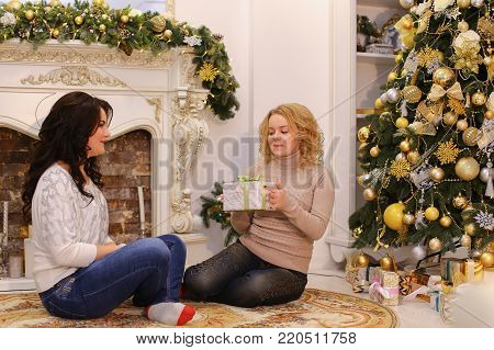 Blonde girl has prepared holiday gift for girlfriend and happily hands her, brunette eager to find out what's inside, shakes box and pulls for bow. Women are sitting on floor on beautiful carpet in spacious and bright living room with fireplace and mirror