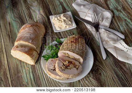 Roll of chicken fillet with stuffing edible chestnuts, bacon, cheese and spices is in a plate, on a wooden table close-up (Greek cuisine).