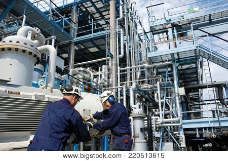 oil and gas refinery workers inside large industrial plant