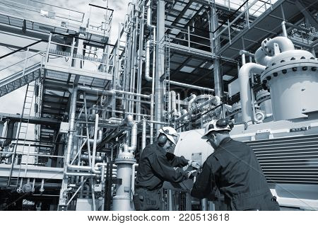 oil and gas workers inside large refinery, pipelines and pumps