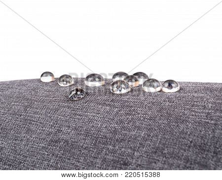 Gray waterproof fabric with waterdrops close up on white background