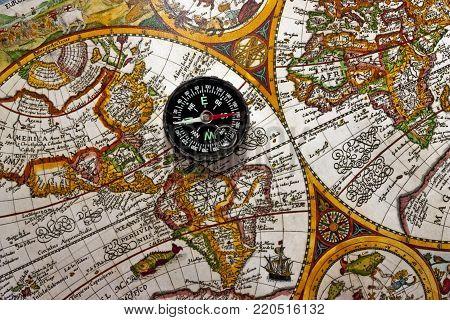 Soviet miniature compass on an ancient world map.