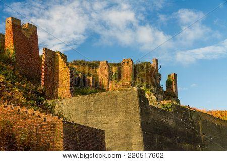 Derelict brick hoppers in Sunshine. Porthgain, Pembrokeshire, Wales, United Kingdom.