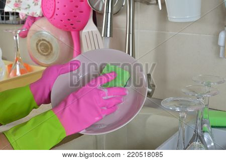 Washing a pink plate  wearing rubber pink gloves above a kitchen sink