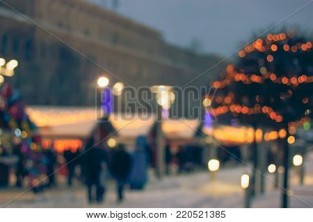 Colorful bokeh defocused Christmas fair market lights. Blurred background New Year fair.
