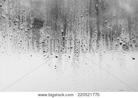 High humidity and condensation in the drops of natural water on the window, temperature drop, cold tone can be used as a background or texture