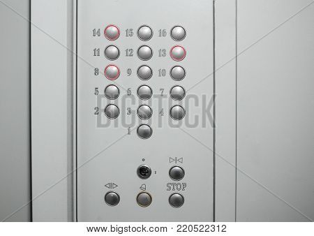 CoControl panel with buttons from the first to the sixteenth floor in the Elevator of gray. Three buttons is pressed and glows redntrol panel with buttons in the lift cabin