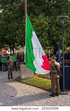 Conegliano, Italy - October 13, 2017: Commemoration ceremony at the monument to the fallen soldiers. Veterans and military are taking part in the event memory. The Flag Of Italy.