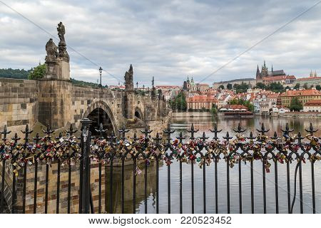 Hundreds of love locks on a fence in Prague, Czech Republic. Charles Bridge (Karluv most), Mala Strana District (Lesser Town) and Prague (Hradcany) Castle are in the background.