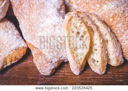 A close-up of sliced bread against a loaf of bread. Rectangular loaves of bread lie on the heap. Bread is sprinkled with flour and lies on the table.
