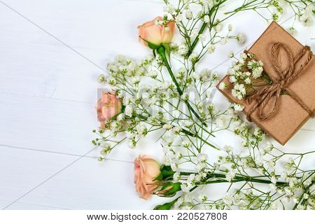 Flowers with a gift box on white wooden table, flat lay style