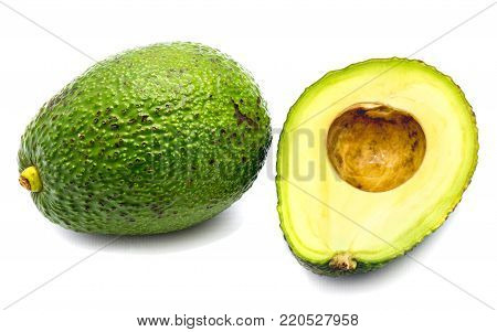 Whole avocado (Persea americana, alligator pear) and its half with a stone isolated on white background