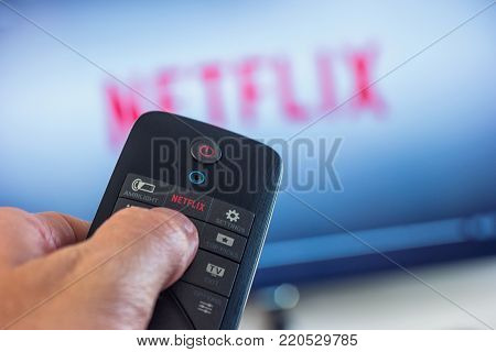 AACHEN, GERMANY OCTOBER, 2017:Man holds a remote control and selects a movie from Netflix. Netflix is an entertainment company, specializes in and provides streaming media and video on demand online.