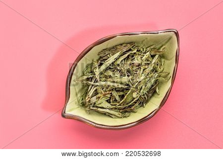 stevia dried leaves on ceramic leaf shape bowl against pink background  - natural sweetener, sugar substitute