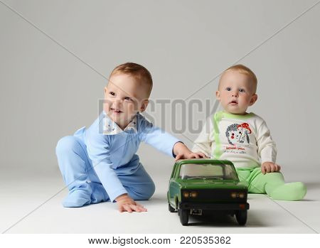 Infant child baby boy kids toddler sitting and playing with green retro car in light blue and green on gray background