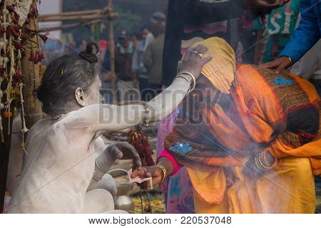 BABUGHAT, KOLKATA, WEST BENGAL / INDIA - 11TH JANUARY 2015 : Hindu Sadhu with white ash applied on body and face, blessing orange coloured dress clad Indian devotee woman.
