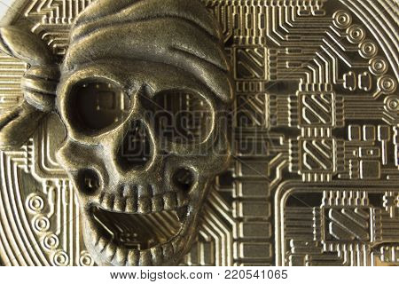 Macro. Metallic face of the pirate skeleton on the background of the reverse side of bitcoin. Super close-up.