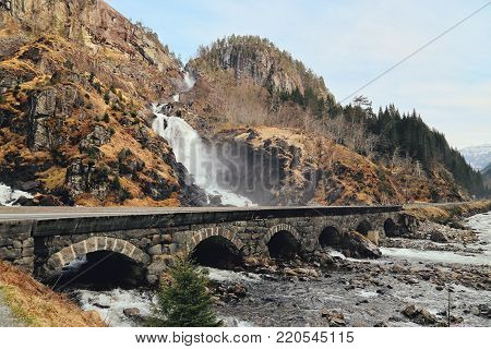 Latefossen Waterfall Odda Norway with the stone road bridge across in spring April season. Latefoss is a powerful, twin waterfall.Latefoss is one of the famous sightseeing waterfall.