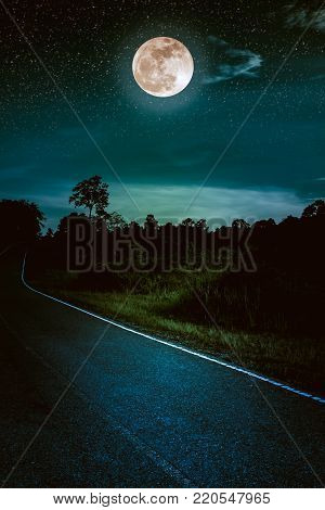 Beautiful landscape of dark sky with bright full moon and asphalt roadway through suburban zone. Serenity nature background, outdoor at nighttime. The moon taken with my own camera.