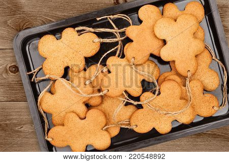 Baking sheet with gingerbread men on dark wooden background closeup