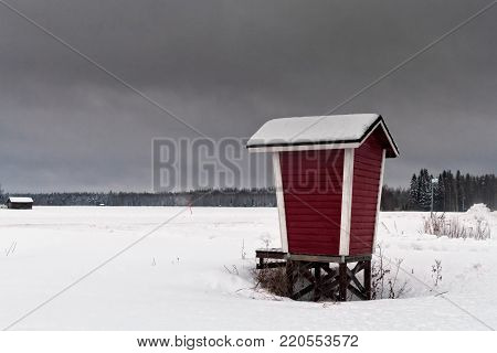 A wooden shelter for milk containers stands by the snowy fields at the rural Finland. The frost has covered the fields, the forest and the shelter.