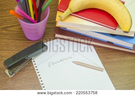 Studying table with pencils, books, banana and other accessories